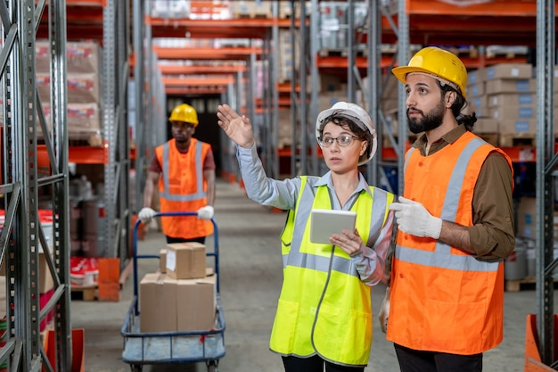 Zajęci młodzi pracownicy magazynu w strojach odblaskowych stojący w przejściu i omawiający rozmieszczenie przedmiotów