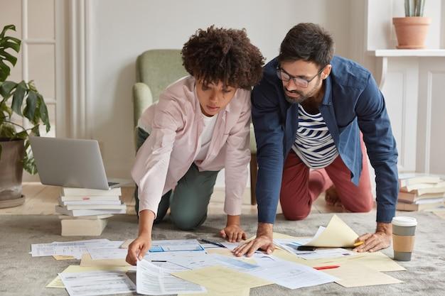 Zajęci młodzi współpracownicy stoją na kolanach na podłodze