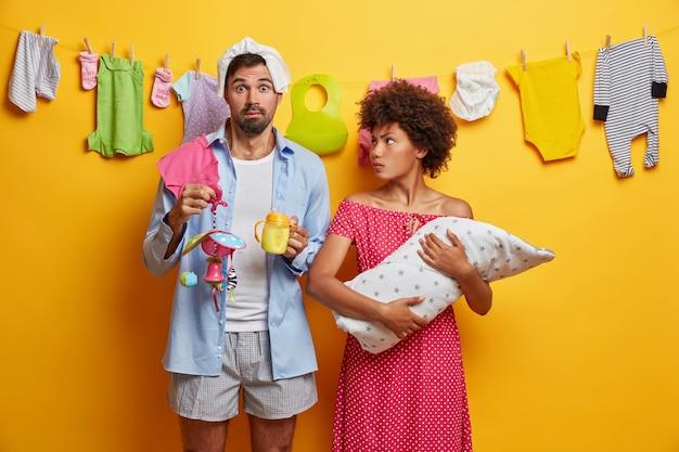Zajęci rodzice karmią dziecko. młoda para doświadcza rodzicielstwa. noworodek w rękach troskliwej matki. zszokowany ojciec trzyma na głowie butelkę do karmienia i telefon komórkowy, pieluchę. rodzicielstwo, koncepcja rodziny