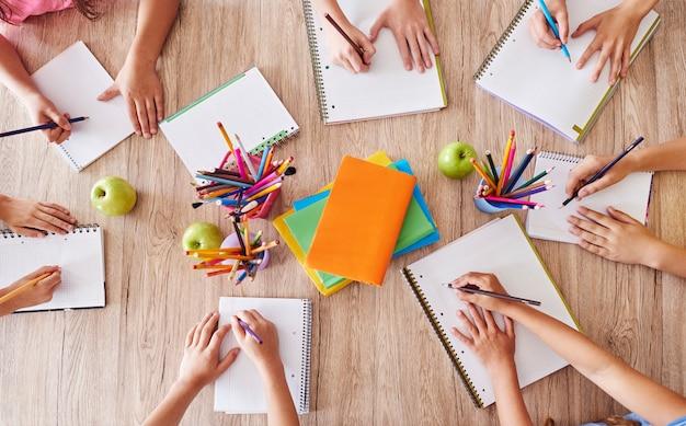 Zajęci uczniowie przy jednym stole