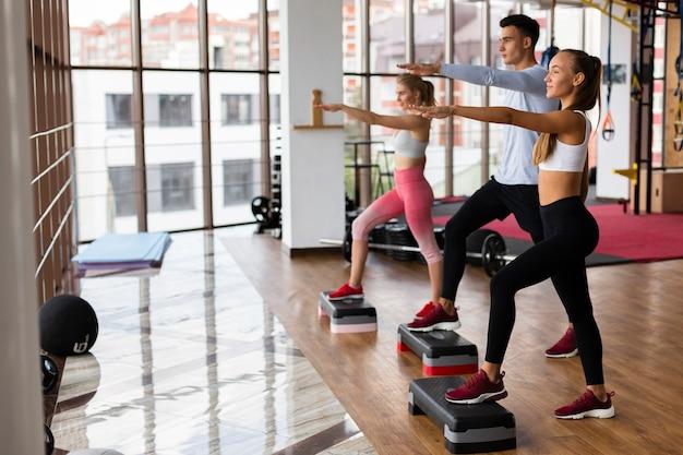Zajęcia grupowe fitness na siłowni z wysportowanymi młodymi