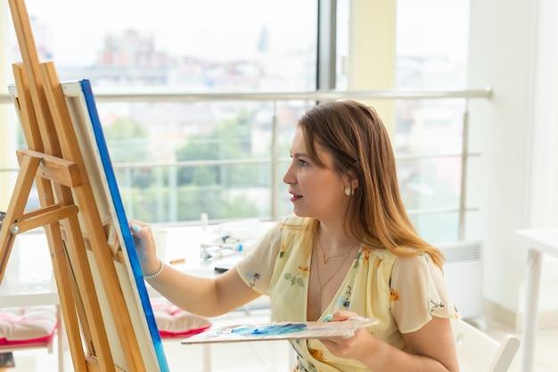 Zajęcia malarskie. kursy rysunku. umiejętności wyobraźnia i inspiracja. urocza studentka tworząca obraz na sztalugach.