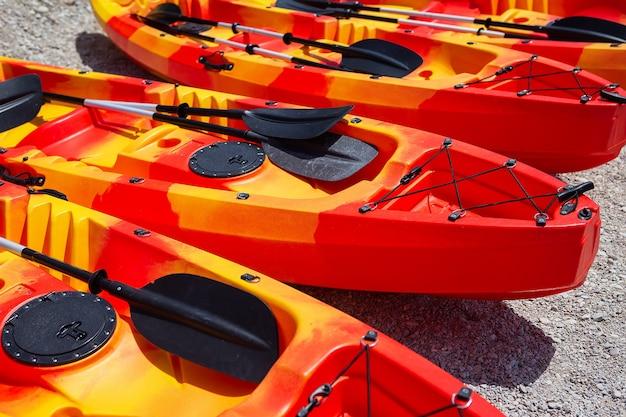 Zajęcia rekreacyjne, sportowe, kajaki. łódź do raftingu. na piaszczystej plaży jest kilka jasnopomarańczowych kajaków.