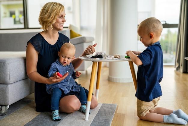 Zajęcia rodzinne w pokoju dziecięcym. kobieta i dzieci bawiące się razem. zabawa, koncepcja edukacji.