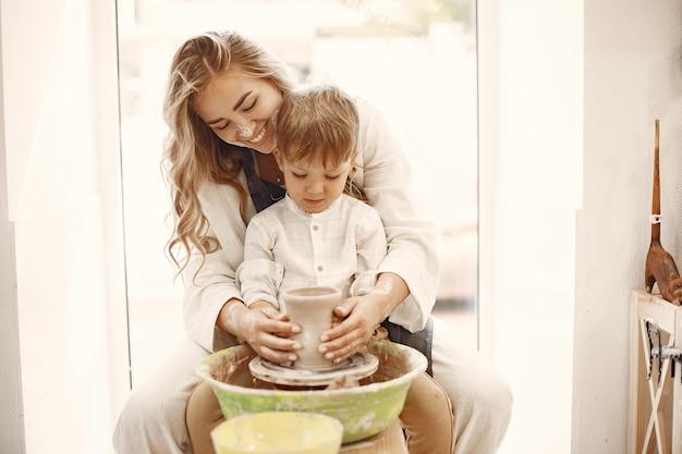 Zajęcia z ceramiki. młoda kaukaska matka uczy syna. syn robi gliniany garnek na kole garncarskim.