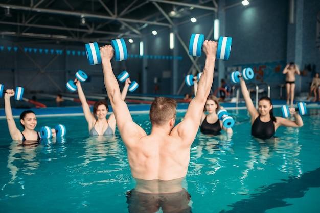 Zajęcia z trenerem na treningu z hantlami w wodzie