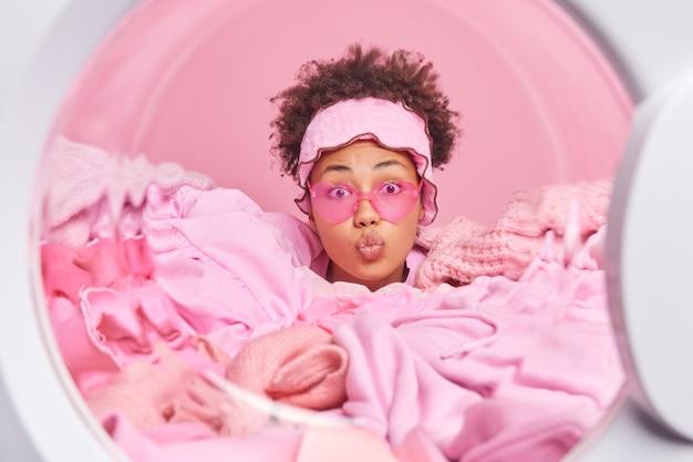 Zajęta gospodyni domowa z kręconymi włosami trzyma usta złożone i nosi modne okulary przeciwsłoneczne ładuje automatyczną pralkę zakopaną w stosie ubrań na różowej ścianie