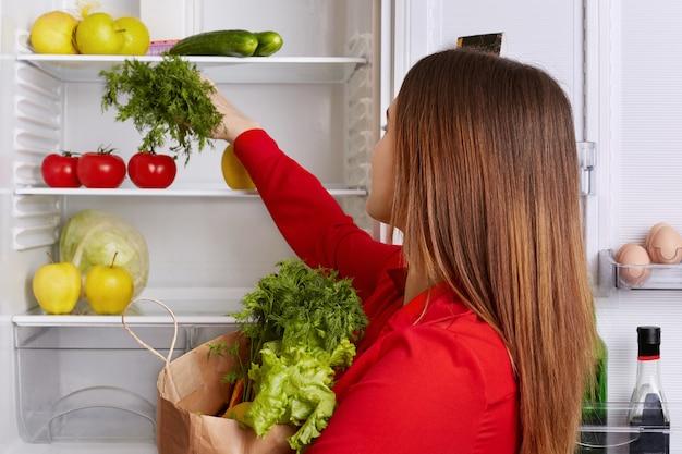Zajęta gospodyni stawia świeże warzywa, które właśnie kupiła na półce lodówki