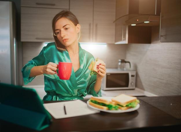 Zajęta kobieta je, pije kawę, rozmawia przez telefon, pracuje jednocześnie na laptopie. kobieta robi wiele zadań