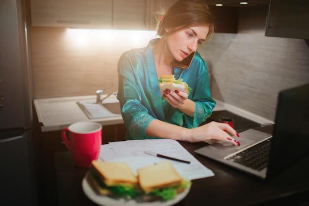 Zajęta kobieta je, pije kawę, rozmawia przez telefon, pracuje na laptopie w tym samym czasie. bizneswoman robi wiele zadaniom. wielozadaniowość przedsiębiorca. freelancer pracuje w nocy.