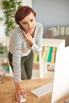 Zajęta kobieta pochylająca się nad biurkiem