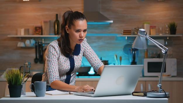 Zajęta kobieta pracuje w nocy z domu i robi notatki z laptopa, pisząc na notebooku. zapracowany, skoncentrowany pracownik korzystający z nowoczesnej technologii bezprzewodowej, wykonujący nadgodziny w celu czytania pracy, pisania, wyszukiwania
