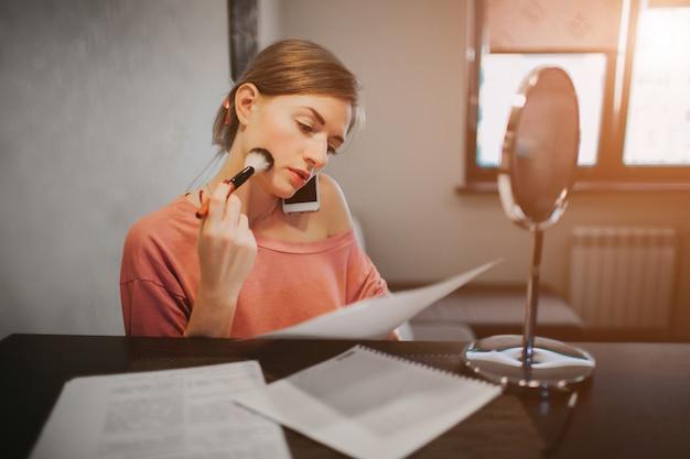 Zajęta kobieta robi makijaż, rozmawia przez telefon, jednocześnie czyta dokumenty. bizneswoman robi wiele zadaniom. wielozadaniowość przedsiębiorca.
