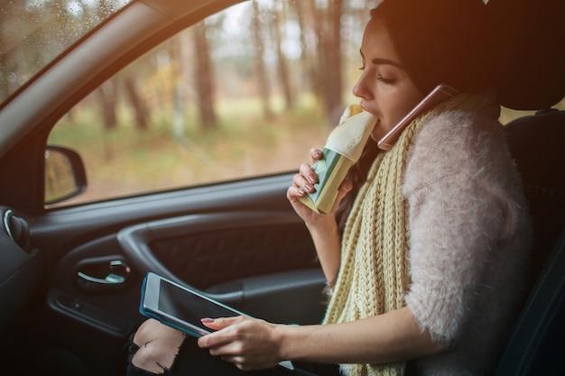 Zajęta kobieta się spieszy, nie ma czasu, będzie jadła przekąskę w drodze. pracownik je i rozmawia przez telefon w tym samym czasie.