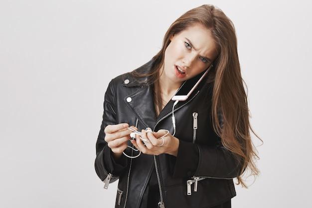 Zajęta kobieta trzyma smartfon na szyi, próbując rozwiązać przewodowe słuchawki