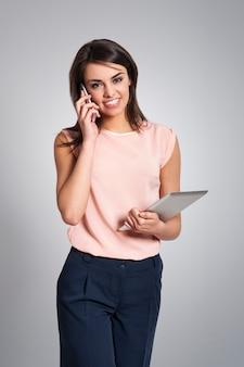Zajęta kobieta ze sprzętem elektronicznym