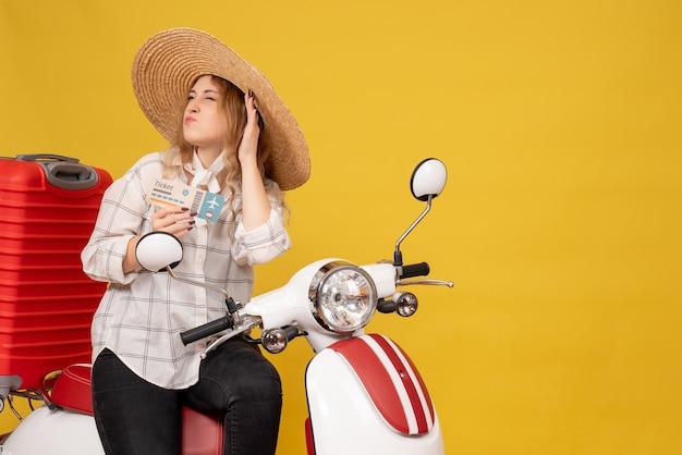 Zajęta młoda kobieta w kapeluszu i siedzi na motocyklu i trzymając bilet słuchając ostatniej plotek na żółto