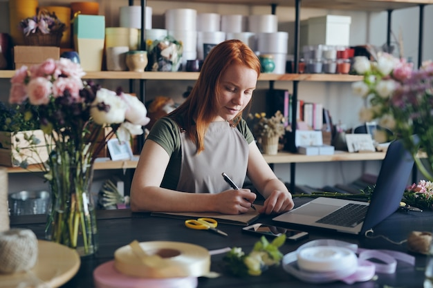 Zajęta młoda kobieta z rudymi włosami, stojąca przy blacie i robiąca notatki w szkicowniku, używając laptopa do kupowania kwiatów online do własnego sklepu
