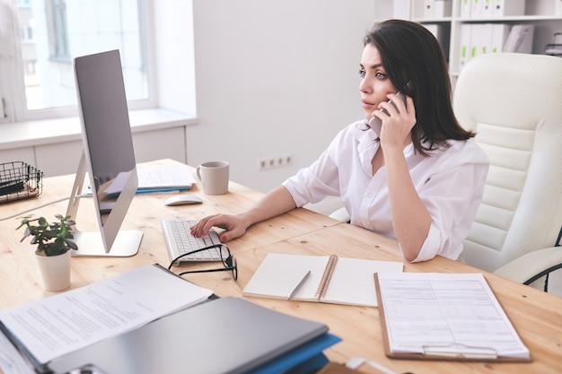 Zajęta młoda sekretarz firmy konsultingowej z klientami przez telefon, wykonując swoją pracę przed monitorem komputera w biurze