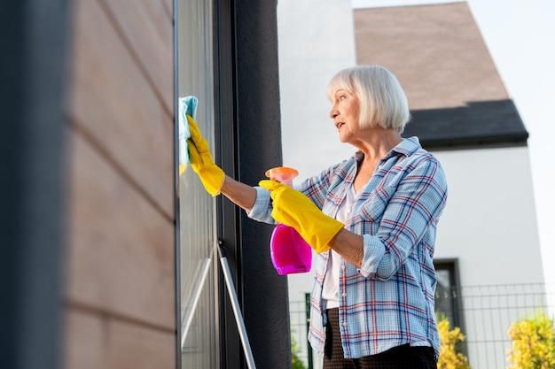 Zajęta pani. starsza piękna pani w jasnożółtych rękawiczkach czuje się wyjątkowo zajęta myciem okien