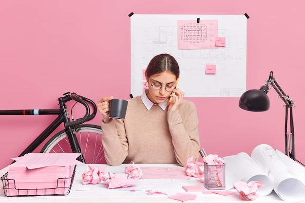 Zajęta studentka pracuje nad zadaniami domowymi, rozmawia z kolegą z grupy, dyskutuje, pije kawę, nosi zwykłe ubrania, koncentruje się na pracach zaangażowanych w proces pracy. uczennica robi raporty, tworzy szkice
