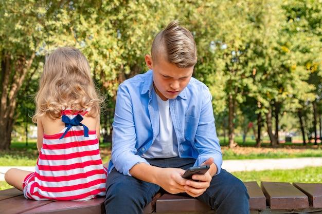 Zajęte dzieciaki patrzą na telefony, wysyłają sms-y i bawią się na zewnątrz