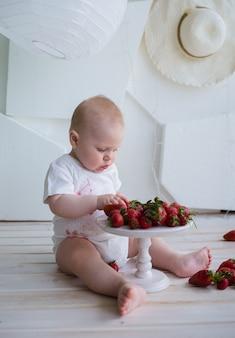 Zajęte dziecko siedzi na podłodze i je truskawki na białej powierzchni z miejscem na tekst