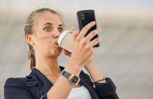 Zajęty biznes kobieta pije kawę, patrząc na jej telefon komórkowy