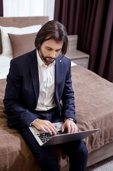 Zajęty biznesmen. inteligentny przystojny mężczyzna pisze na swoim laptopie podczas pracy z pokoju hotelowego