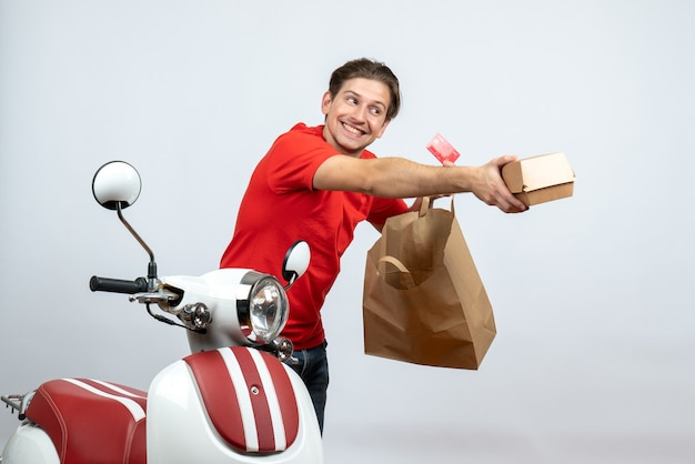 Zajęty człowiek dostawy w czerwonym mundurze, stojący w pobliżu skutera i trzymając zamówienia kart bankowych na białym tle