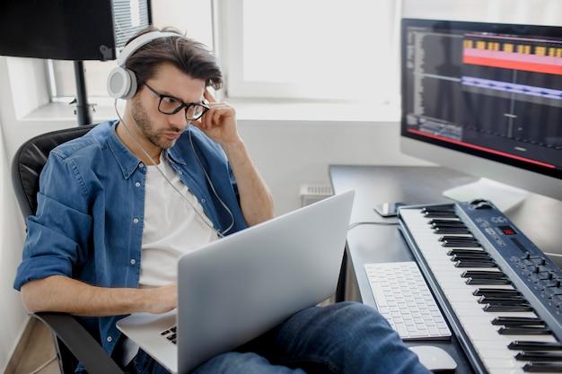 Zajęty człowiek pracuje na laptopie w studio