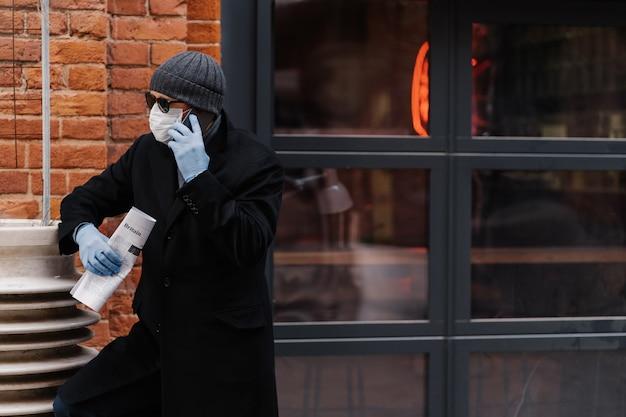 Zajęty człowiek rozmawia przez telefon, koncentruje się na boku, omawia najnowsze wiadomości, trzyma gazetę, chroni się podczas rozprzestrzeniania się wirusa pandemii. ochrona przed koronawirusem. pojęcie opieki zdrowotnej