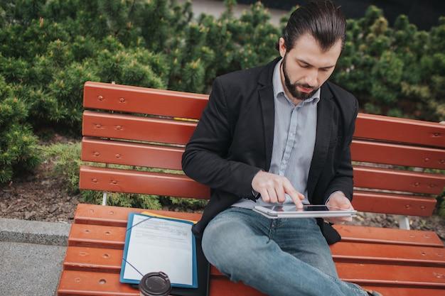 Zajęty człowiek się spieszy, nie ma czasu, zamierza zjeść przekąskę na świeżym powietrzu. pracownik jednocześnie je i pracuje z dokumentami na komputerze typu tablet. biznesmen robi wiele zadań.