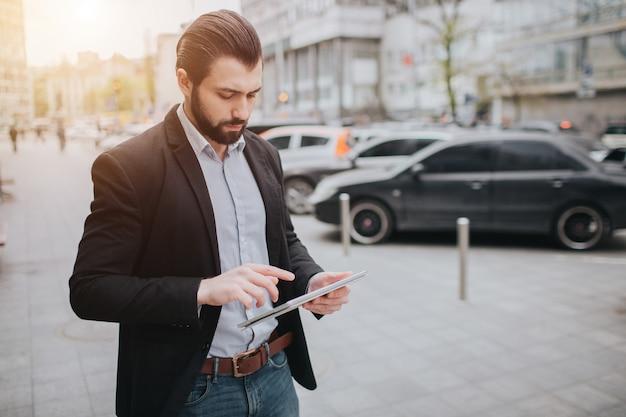Zajęty człowiek śpieszy się, nie ma czasu, będzie korzystał z komputera typu tablet w podróży. biznesmen robi wiele zadań. wielozadaniowość przedsiębiorca.