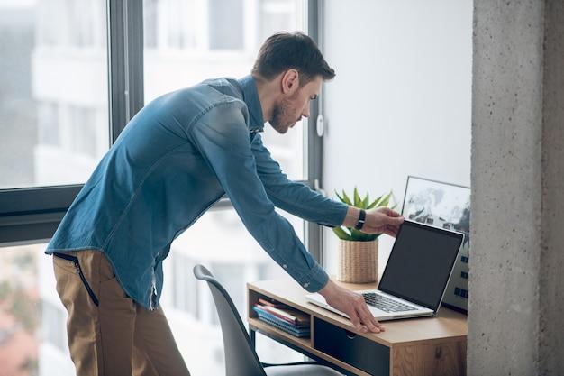 Zajęty dzień. młody mężczyzna pracujący w biurze i patrząc zajęty
