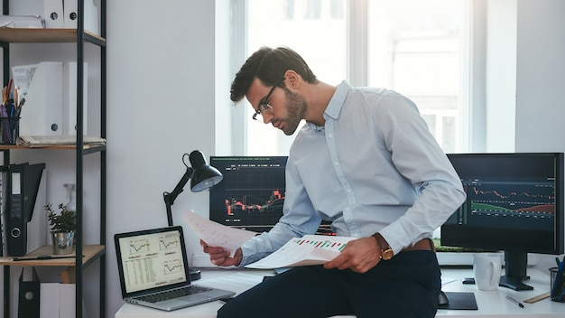 Zajęty dzień roboczy młody odnoszący sukcesy handlowiec lub biznesmen w stroju wizytowym i okularach siedzący w