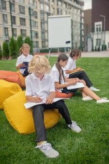Zajęty. grupa uczniów odbywająca lekcje na świeżym powietrzu i wyglądająca na skoncentrowaną