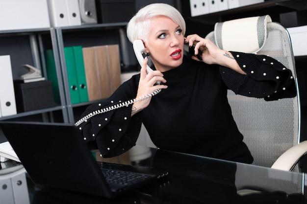 Zajęty kobieta rozmawia z telefonu komórkowego i telefon stacjonarny siedzi przy stole w biurze