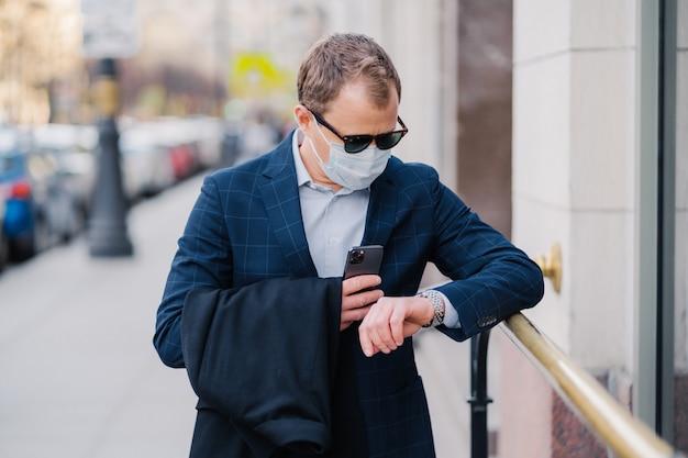 Zajęty mężczyzna czeka na partnera biznesowego, patrzy na pozy zegarka na ulicy. nosi maskę medyczną, chroni przed koronawirusem