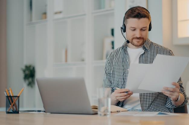 Zajęty mężczyzna freelancer noszący zestaw słuchawkowy, trzymający dokumenty w rękach i pracujący zdalnie na laptopie, siedząc w salonie w domu. koncepcja biznesowa online i freelancer