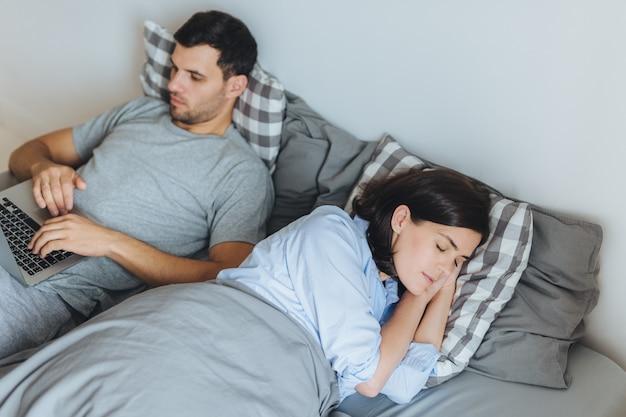 Zajęty mężczyzna leży w łóżku, pracuje na komputerze przenośnym, ma poważny wyraz twarzy, podczas gdy jego żona ma zdrowy sen