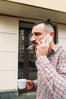 Zajęty mężczyzna rozmawia przez telefon na zewnątrz