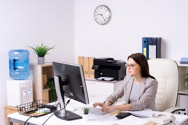 Zajęty młoda kobieta w okularach, wpisując na klawiaturze komputera podczas pracy w nowoczesnym biurze