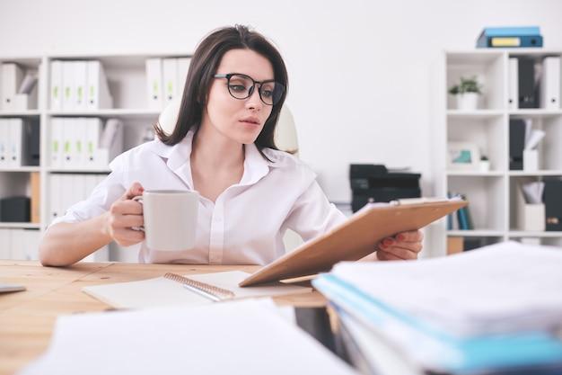 Zajęty młody biuro kobieta siedzi przy stole i czyta dokumenty podczas picia kawy w biurze