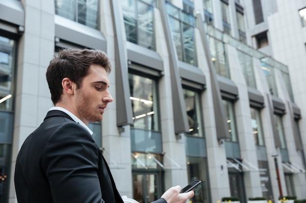 Zajęty młody człowiek pracuje z smartphone