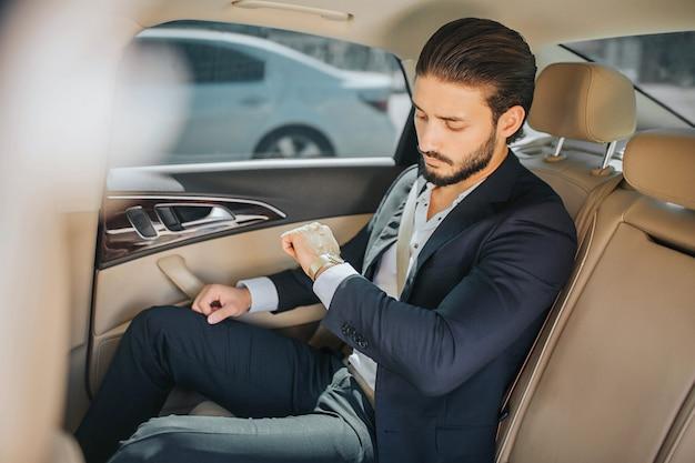 Zajęty młody człowiek siedzi w luksusowym samochodzie i patrząc na zegarki. on jest spóźniony. facet nosi garnitur. jest poważny i skoncentrowany.