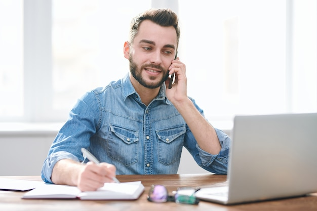 Zajęty młody człowiek w casual, siedząc przy biurku przed laptopem, robiąc notatki w notatniku i rozmawiając z klientem przez telefon