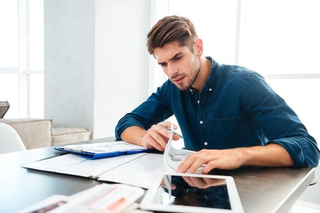 Zajęty młody człowiek w domu, analizując swoje finanse w domu, siedząc w pobliżu tabletu