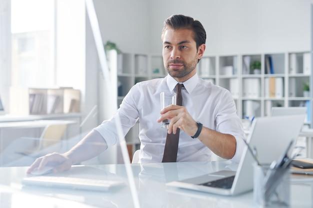 Zajęty młody handlowiec elegancki, mając szklankę wody, patrząc na ekran komputera podczas pracy w sieci