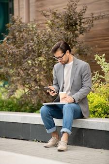 Zajęty młody menedżer w elegancki dorywczo za pomocą smartfona przy kawie na świeżym powietrzu rano